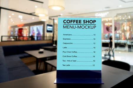 Mock up vertical blank menu in coffee shop   in acrylic frame placed on table, blue screen empty space for insert list menu and price