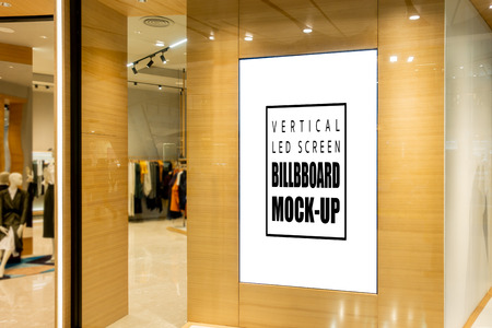 Mock up blank vertical LED screen advertising   at the entrance of fashion shop, empty space to insert media advertisement