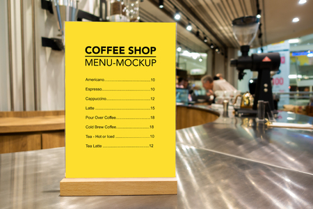 Mock up vertical blank menu in coffee shop  in acrylic and wooden frame placed on counter bar, yellow screen empty space for insert list menu and price Banco de Imagens
