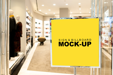 Mock up blank signboard   in metal frame at entrance to clothing shop of woman in shopping mall, yellow screen empty space with stand for insert text advertising