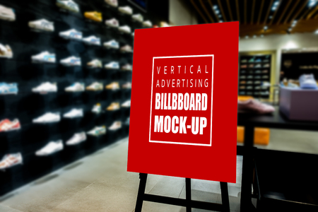 Mock up perspective of vertical advertising billboard   on wooden stand in showroom of sport shoe, red screen empty space for insert text and price Banco de Imagens