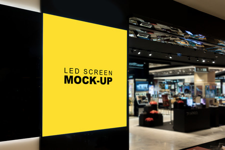 Mock up blank LED billboard for advertising on black backdrop , yellow empty space for multi media or information for promotion at front of IT shop in mall