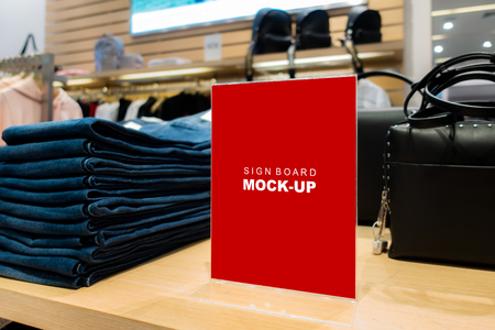 Mock up blank signboard   on shelf space in fashion clothing at shopping mall, Red screen empty space with acrylic for insert text advertising Banco de Imagens