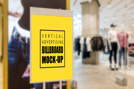 Mock up perspective vertical advertising blank yellow screen billboard   for insert text message content at front of fashion clothing store, marketing and advertisement concept