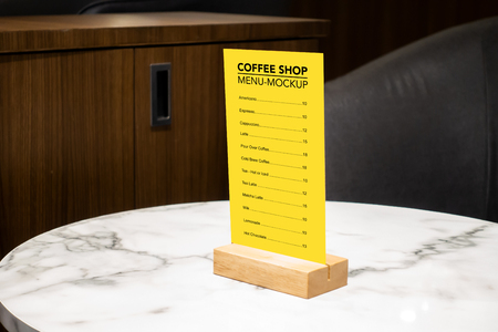 Mock up vertical blank menu in coffee shop  in acrylic and wooden frame placed on marble table, yellow screen empty space for insert list menu and price