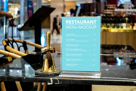 Mock up vertical blank menu in restaurant in acrylic frame and a golden hand held service bell placed nearly on table, empty space for insert text and price Banco de Imagens