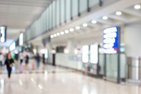 Background image with blurred people walking in airport area nearly gate and information board