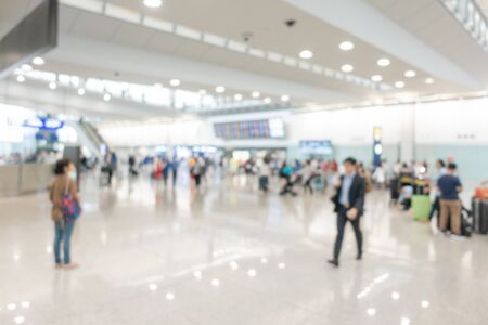 Blurred background image at the airport hall, many traveller walking or standing around area, arrivals board show on the wall near escalator