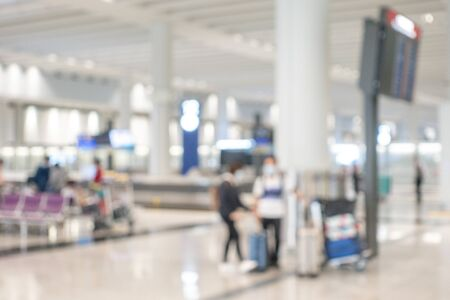 Blurred background image with the departure lounge at airport hall, passenger standing near big pole for waiting at appointment zone Banco de Imagens