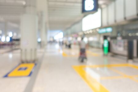 Blurred background image at the airport hall, the passenger with luggage walking in gate area