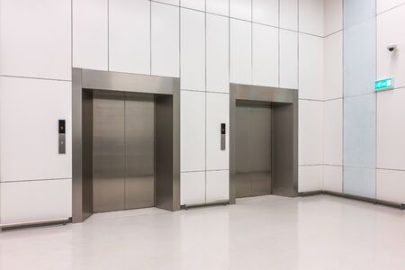 Perspective image of modern steel elevator cabins with closed doors in the business lobby