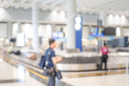 Blurred background with  the carousel or baggage reclaim in baggage hall of airport, the passenger walking and staff working in area, copy space to insert text