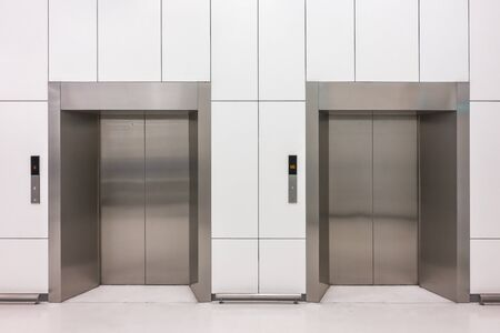 Front view of modern steel elevator cabins with closed doors at business lobby