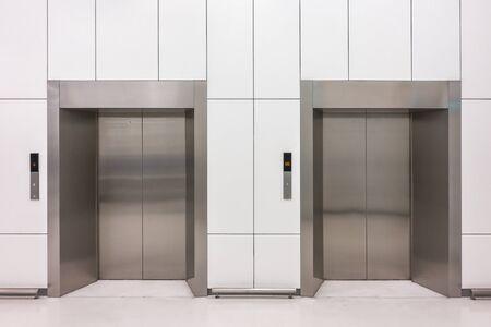 Vooraanzicht van moderne stalen liftcabines met gesloten deuren bij bedrijfslobby