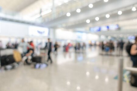 Blurred backgrund image with many traveller walking with luggage in airport hall Banco de Imagens