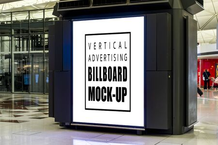 Mock up perspective large vertical billboard with on panel of booth at hall of terminal airport, empty space for advertising or information