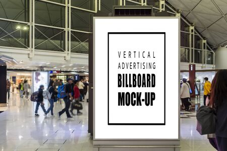 Mock up front view blank vertical billboard advertising with standing in airport terminal hall, passengers walking around area, empty space for advertisement or information