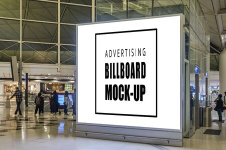 Mock up large blank billboard with on panel of elevator on walkway in hall of airport area, empty space for advertising or information, advertising concept, blurred people walking in background