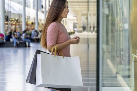 Young female holding two bag, mockup blank screen paper shopping bag with clipping path, Empty space on shopping bag for design insert logo or graphic.