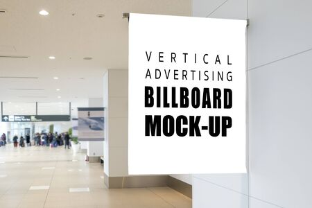 Mock up vertical signboard on the wall over walkway in airport, empty space for insert advertising or announcement information, blurred people on background