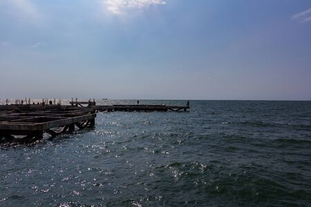 The seashore with the remains of an old jetty located at sea.