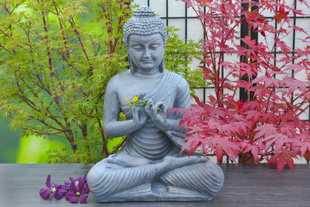 buddha statue with flower decorations and maple trees