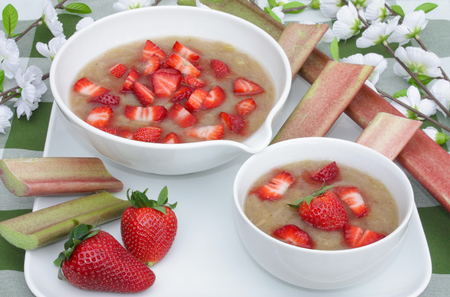 rhubarb compote with strawberries in a bowl with decorations on a table