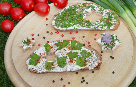 Slices of bread with cream cheese on wooden background with tomato and peppercorn decorations
