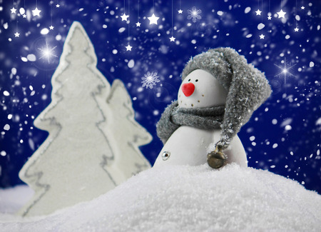 funny snowman in a snowy winter landscape with snow flakes and shining stars Standard-Bild