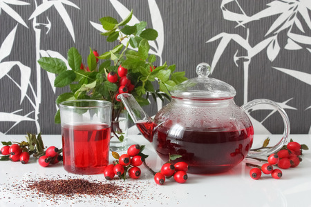 teapot and glass with rosehip tea and rosehip decorations