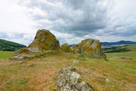 mystical landscape with hills, rocks, meadows, forests and dramatic clouds Standard-Bild