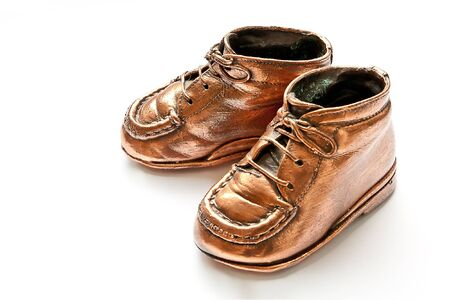 copper coated: Babyshoes in bronze, on white background