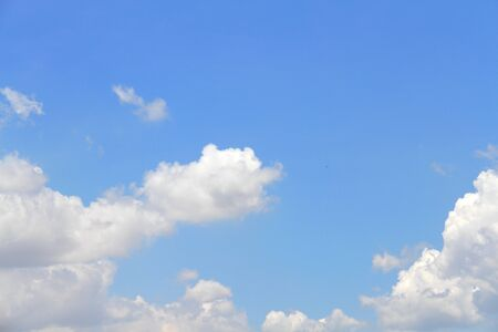 sparse: white fluffy clouds in the blue sky