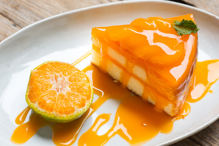 cakes and pastries: orange cake with orange topping in wooden dish Stock Photo