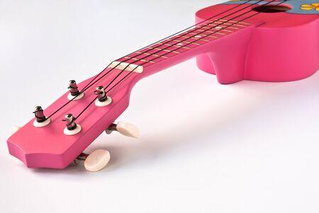 Closeup shot of a Pink Hawaiian ukulele on white background  photo