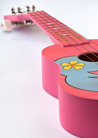 Closeup shot of a Pink Hawaiian ukulele on white background  photo