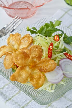 Modern thai food, Deep fried frowers with sour and spicy green mango salad. photo