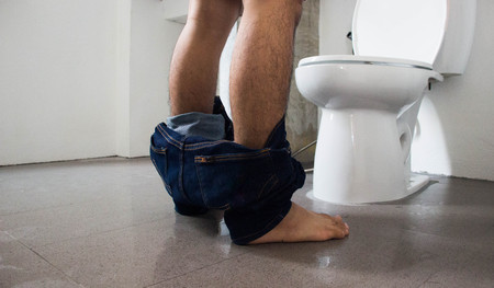 mensroom: Man standing pee Stock Photo