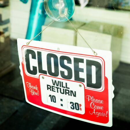 store sign: Vintage retro looking Closed sign in a shop showroom with reflections