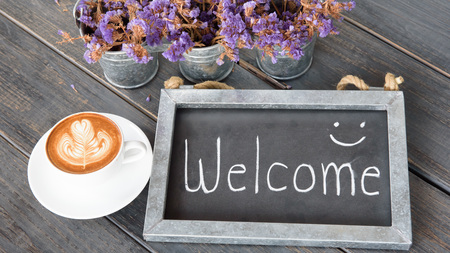 wooden vintage frame WELCOME next to coffee cup