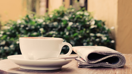 periodicals: A cup of coffee on the table with newspaper