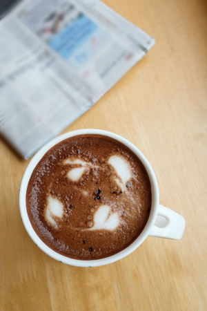 A cup of coffee on the table with newspaper