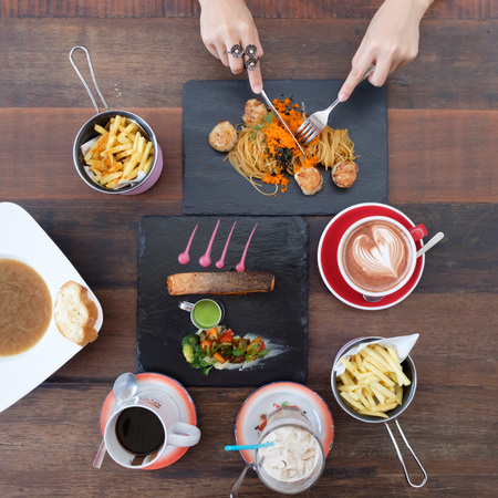 four people: Top view of a woman having food Stock Photo