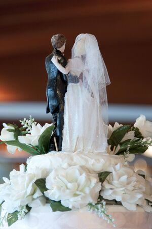Figurines of bride and groom on a wedding cake, backside photo