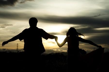 siluetas de enamorados: Silueta de pareja al atardecer  Foto de archivo