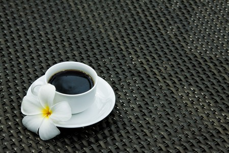 Black coffee with plumeria flower photo
