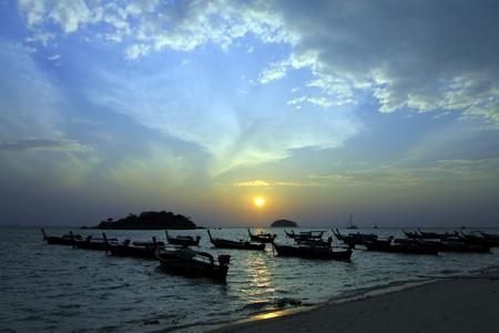 Longtail boats on seashore at sunrise, Lipe island, South of Thailand