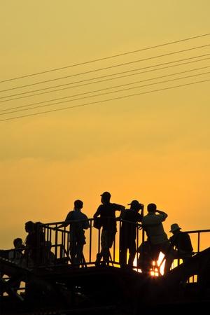 Tourist silhouette, Kwai river bridge, Kanchanaburi Province, Thailand  Stock Photo