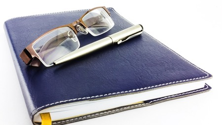 Notebook glasses and pen  isolated on white background  photo