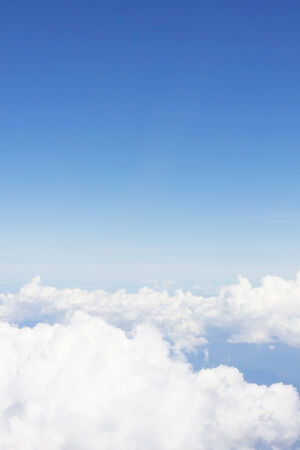 White fluffy clouds in the blue sky looking through on the airplane window  photo